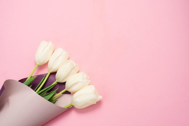 Bukiet białych tulipanów owiniętych w różowy papier. minimalistyczny charakter leżał płasko. kartkę z życzeniami na dzień matki i 8 marca. koncepcja przetargu wiosennych wakacji