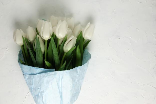 Bukiet białych tulipanów w niebieskim papierze do pakowania na białym tle betonu