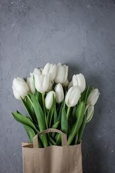 Bukiet białych tulipanów w papierowej torebce kraft na szarym tle betonu
