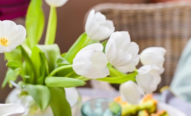 Bukiet białych tulipanów w wazonie na szarym tle. kwiaty jako prezent dla ulubionej osoby. skopiuj kopię.