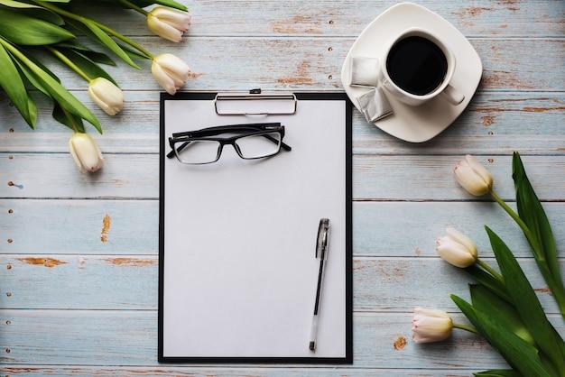 Bukiet białych tulipanów z pustym schowkiem i filiżanką kawy na drewnianym stole