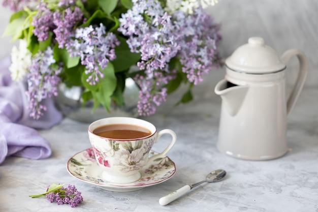 Bukiet bzów, filiżanka kawy
