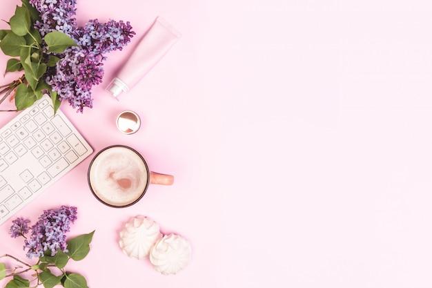 Bukiet bzów, klawiatura, filiżanka kawy, ciastka, krem do twarzy na różowym płaskowniku