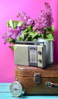 Bukiet bzów w emaliowanym czajniku na antycznej walizce, vintage radio, budzik na różowym tle. martwa natura w stylu retro
