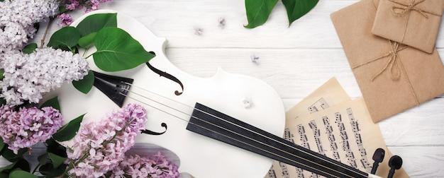 Bukiet bzu ze skrzypcami, listem i nutami na białym drewnianym stole. top wiev z miejscem na tekst.