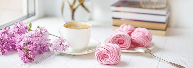 Bukiet bzy, filiżanka kawy, domowej roboty marshmallow i sterta książki na nadokiennym parapecie