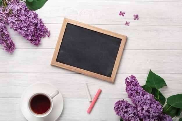 Bukiet bzy z filiżanką herbata, kredowa deska na białych deskach