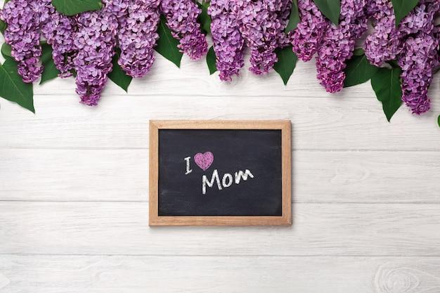 Bukiet bzy z kredową deską na białych deskach. dzień matki