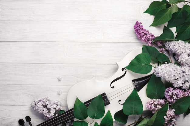 Bukiet bzy z skrzypce i muzyczny prześcieradło na białym drewnianym stole. najlepsze wiev z miejscem na tekst.
