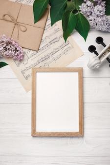 Bukiet bzy z skrzypce, kredowa deska i muzyczny prześcieradło na białym drewnianym stole. najlepsze wiev z miejscem na tekst