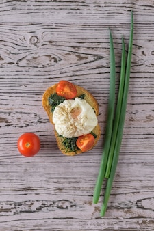 Bukiet cebuli i tosty z jajkiem w koszulce na drewnianym stole. wegetariańska przekąska z jajkiem w koszulce. widok z góry.