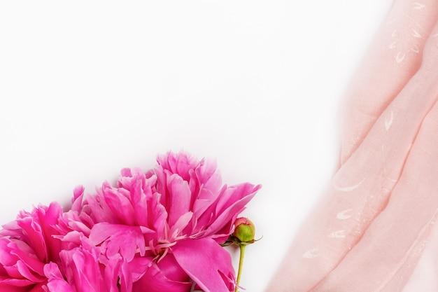Bukiet ciemnoróżowych kwiatów piwonii z bliska i różowa tkanina na białym tle z miejscem na kopię