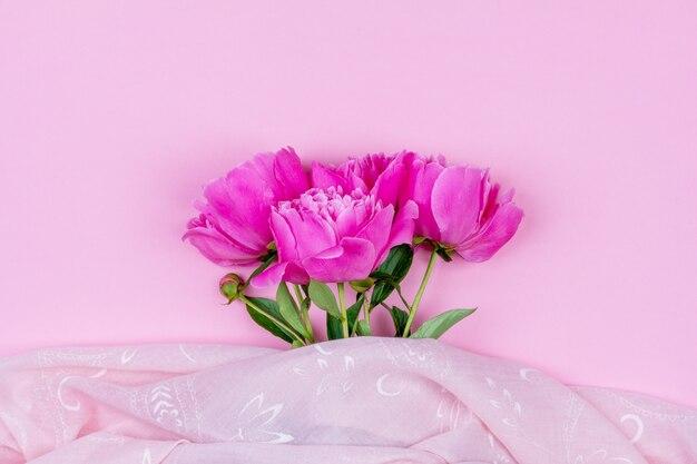 Bukiet ciemnoróżowych kwiatów piwonii z bliska i różowa tkanina na różowym tle z miejscem na kopię
