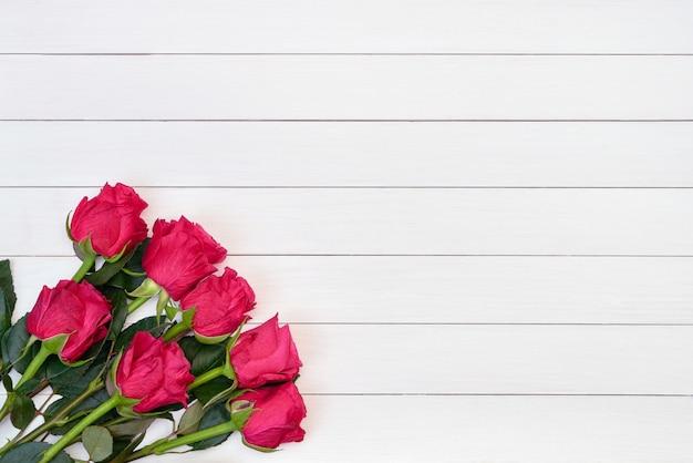 Bukiet czerwone róże na białym drewnianym tle. widok z góry, kopia przestrzeń