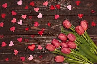 Bukiet czerwoni tulipany na drewnianym tle z czerwonymi sercami. Koncepcja Walentynki. Skopiuj miejsce.