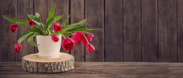 Bukiet czerwoni tulipany na drewnianym tle