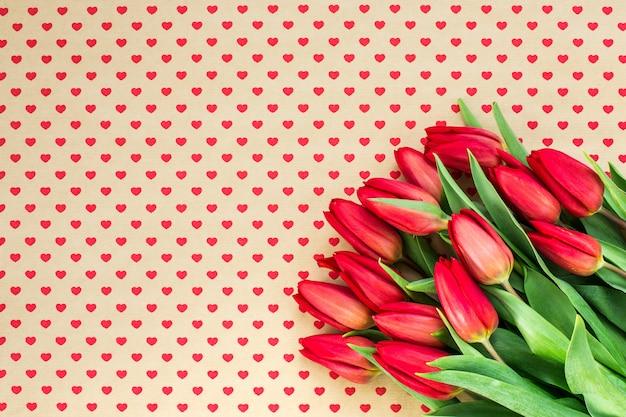 Bukiet czerwoni tulipany na serca tle. skopiuj przestrzeń, widok z góry.