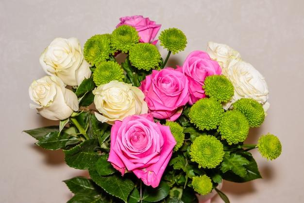 Bukiet czerwonych, białych róż i chryzantem o ciemnozielonych liściach.