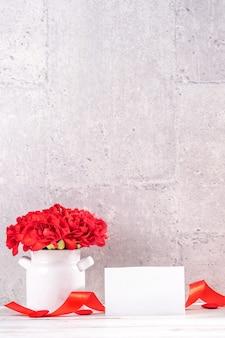 Bukiet czerwonych goździków w wazonie na powitanie koncepcji dnia matki.