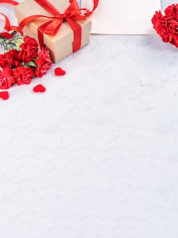 Bukiet czerwonych goździków z pudełkiem na powitanie koncepcji dnia matki.