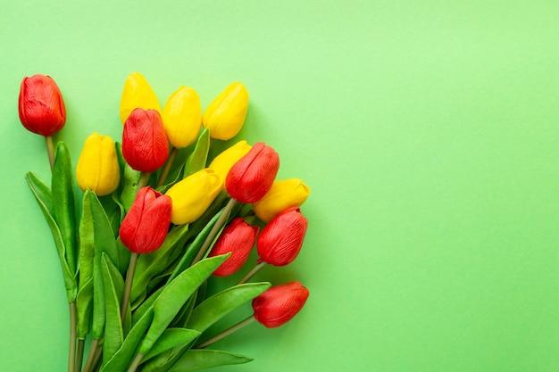 Bukiet czerwonych i żółtych tulipanów na zielonym tle. skopiuj miejsce