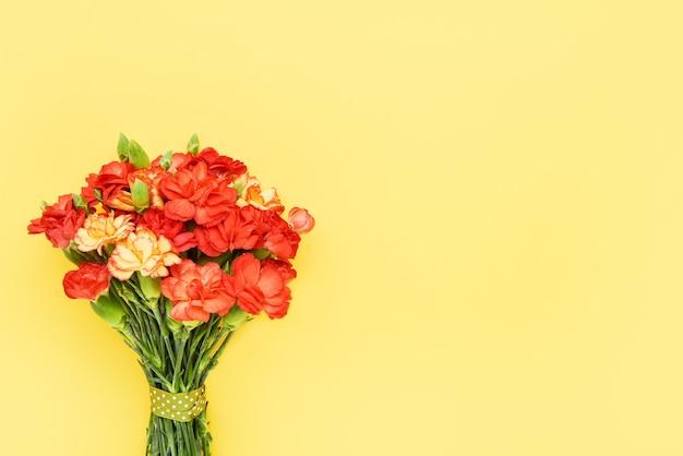 Bukiet czerwonych kwiatów goździka na żółtym tle obchody urodzin walentynki dzień matki