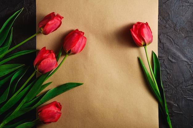 Bukiet czerwonych kwiatów tulipanów na teksturowanym brązowym papierze