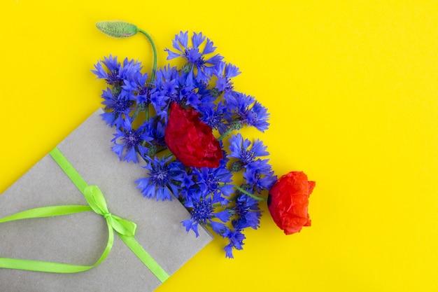 Bukiet czerwonych maków i niebieskich chabrów w kopercie na żółto
