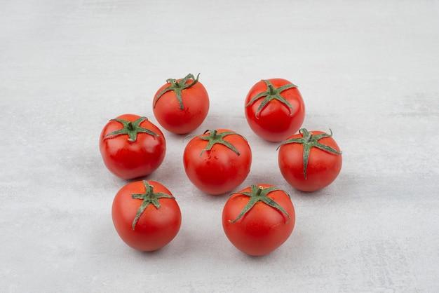 Bukiet czerwonych pomidorów na białej powierzchni.