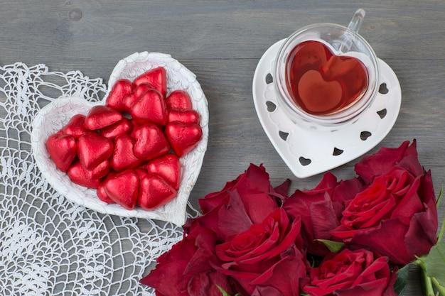 Bukiet czerwonych róż, cukierków w kształcie serca i herbaty w filiżance