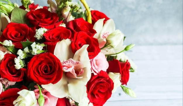 Bukiet czerwonych róż, eustoma, orchidea. martwa natura z kolorowymi kwiatami. walentynki z różami