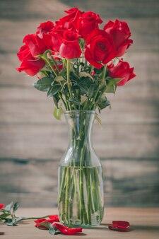 Bukiet czerwonych róż i płatki z wazonem