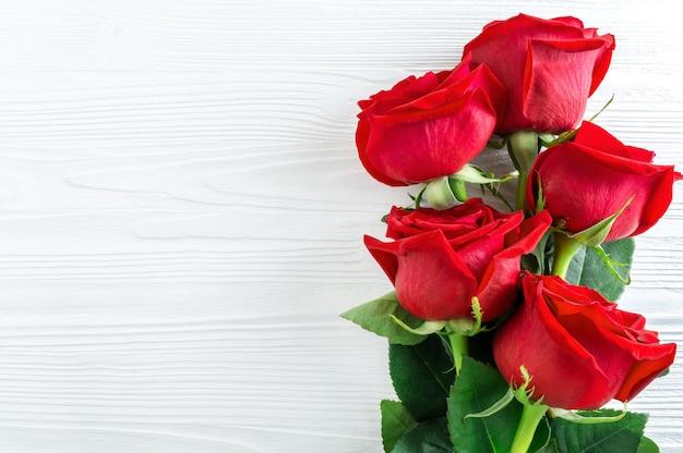 Bukiet czerwonych róż na białym drewnianym tle.