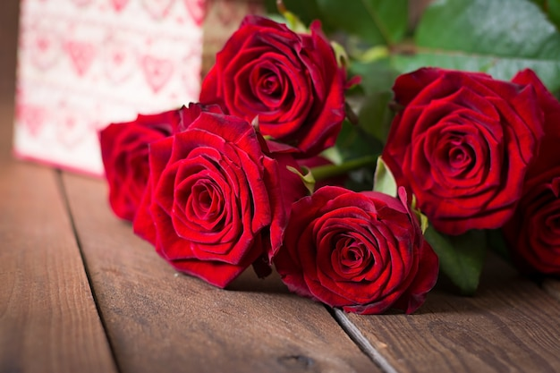 Bukiet czerwonych róż na drewnianym stole.