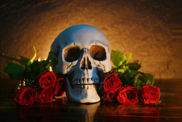 Bukiet czerwonych róż na rustykalnym drewnie z czaszką i blaskiem świec. kwiaty róża romantyczna miłość i śmierć walentynki koncepcja