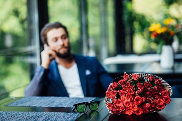Bukiet czerwonych róż na stole, a mężczyzna rozmawia przez telefon z tyłu