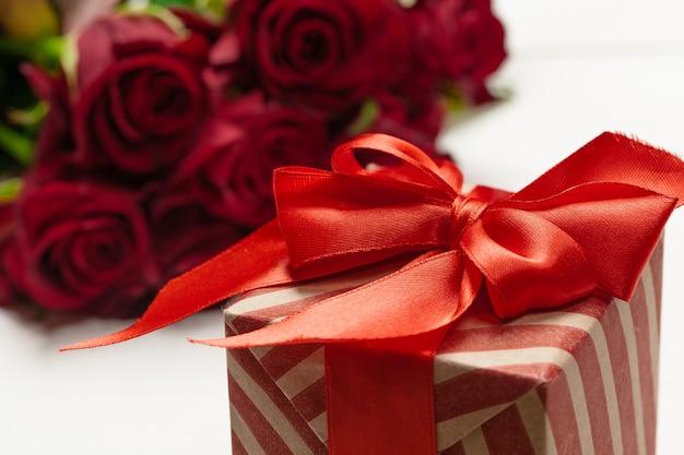 Bukiet czerwonych róż, prezent i serca na stole. koncepcja dnia kobiet lub świętego walentego. skopiuj miejsce