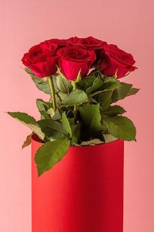 Bukiet czerwonych róż w czerwonym garnku na różowym tle.