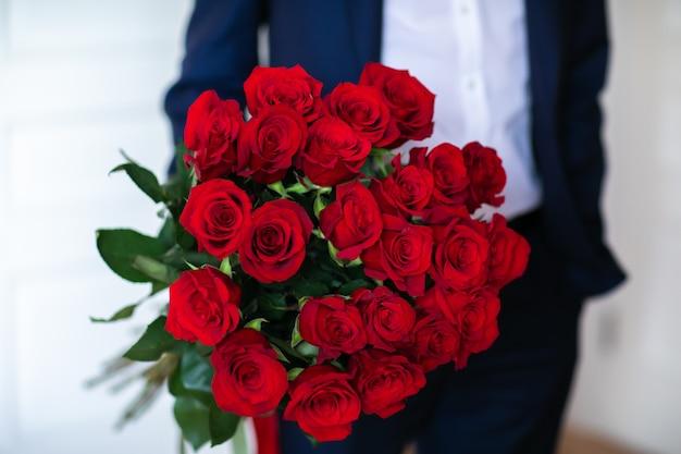 Bukiet czerwonych róż w ręce mężczyzny białe tło. skopiuj miejsce