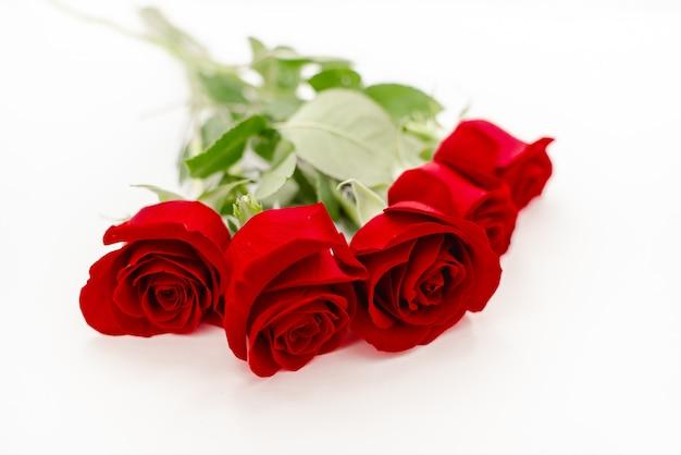 Bukiet czerwonych róż z czerwoną wstążką.