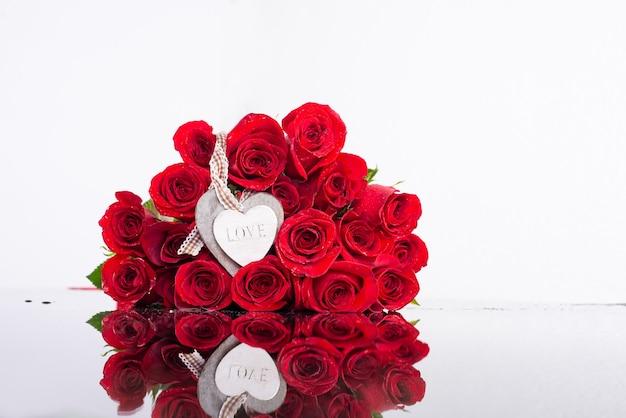 Bukiet czerwonych róż z drewnianym sercem. walentynki tło