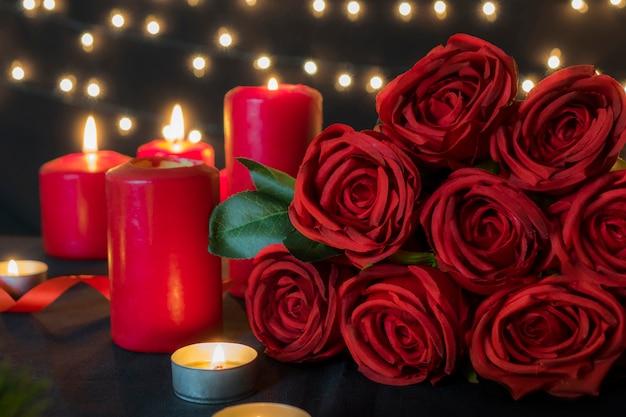 Bukiet czerwonych róż z romantycznymi światłami świec przeciw bokeh dla koncepcji walentynkowej