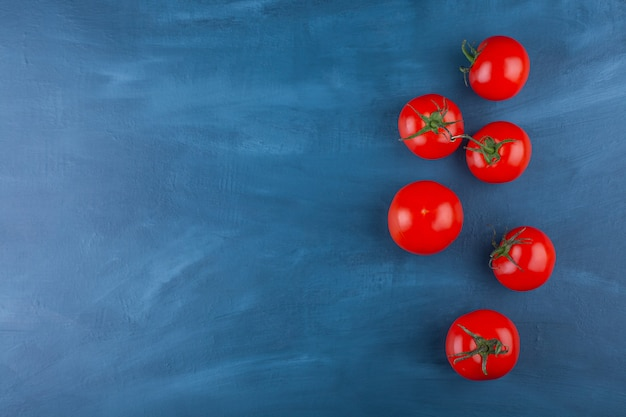 Bukiet czerwonych świeżych pomidorów umieszczony na niebieskiej powierzchni.