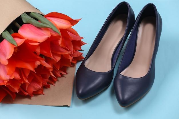 Bukiet czerwonych tulipanów i buty na wysokim obcasie na niebieskim tle. święto matki lub 8 marca, urodziny.