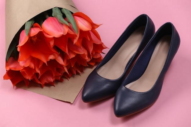 Bukiet czerwonych tulipanów i buty na wysokim obcasie na różowym tle. święto matki lub 8 marca, urodziny.
