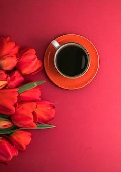 Bukiet czerwonych tulipanów i układ filiżanek kawy z dużą ilością miejsca na tekst