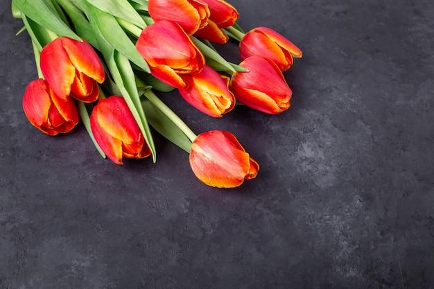 Bukiet czerwonych tulipanów na ciemnym kamiennym stole. skopiuj miejsce