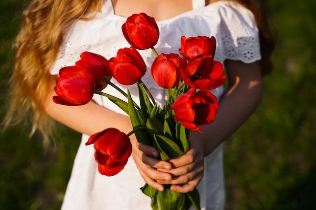 Bukiet czerwonych tulipanów na rękach dziewczyny. zdjęcie wysokiej jakości