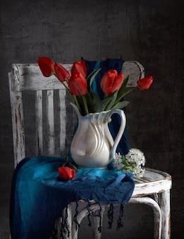 Bukiet czerwonych tulipanów w białym wazonie na vintage cher. walentynki, dzień matki, koncepcja urodziny.