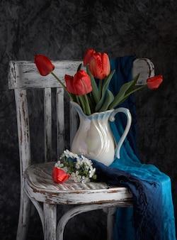 Bukiet czerwonych tulipanów w białym wazonie na vintage cher